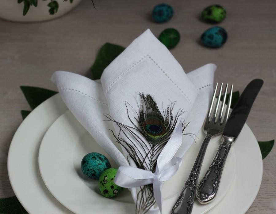 Biała serwetka z pawim piórem i przepiórczymi jajami